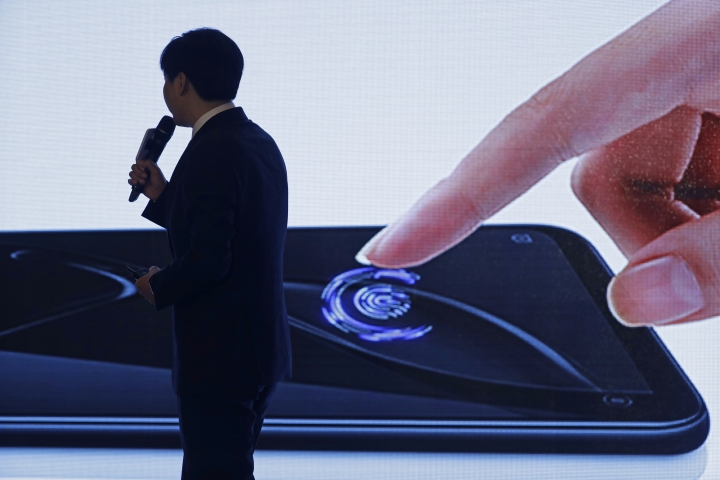 Xiaomi's Founder, Chairman and CEO Jun Lei speaks in front of a screen showing the fingerprint sensor technology at a news conference in Hong Kong, Saturday, June 23, 2018. Xiaomi Corp. said it seeks to raise up to $6.1 billion in its initial public offering next week that would value the Chinese smartphone maker at as much as $70.3 billion. (AP Photo/Kin Cheung)