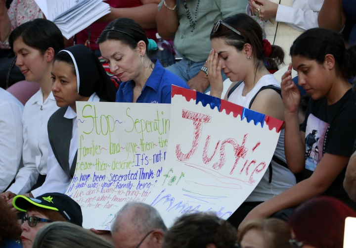 People gather at Saint Mark Catholic Church for a solidarity with migrants vigil, Thursday, June 21, 2018 in El Paso, Texas. President Donald Trump's order ending the policy of separating immigrant families at the border leaves a host of unanswered questions, including what happens to the more than 2,300 children already taken from their parents and where the government will house all the newly detained migrants in a system already bursting at the seams. (AP Photo/Matt York)