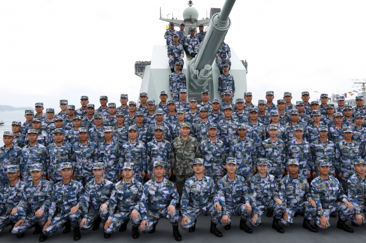 """FILE - In this April 12, 2018, file photo released by Xinhua News Agency, Chinese President Xi Jinping, center in green military uniform, poses with soldiers on a navy ship for a photo after he reviewed the Chinese People's Liberation Army (PLA) Navy fleet in the South China Sea. U.S. Defense Secretary Jim Mattis, who has accused China of """"intimidation and coercion"""" in the South China Sea, is visiting Beijing as the countries increasingly spar over U.S. arms sales to Taiwan and Beijing's expanding military presence overseas. (Li Gang/Xinhua via AP, File)"""