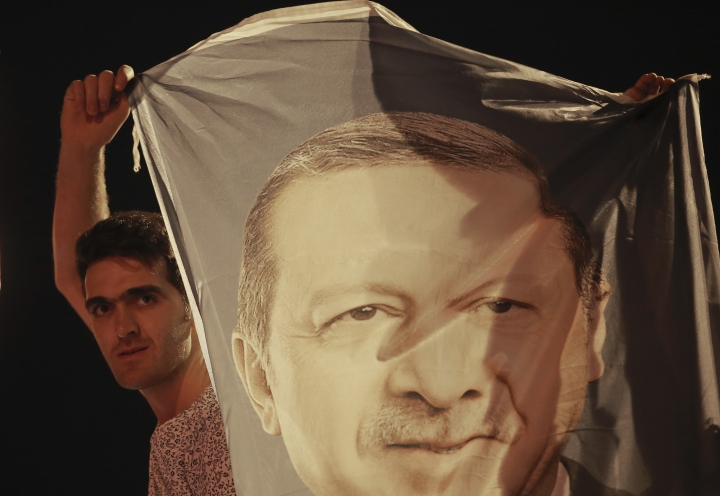 A man holds a banner with a picture of of Turkey's President Recep Tayyip Erdogan celebrate outside his Justice and Development Party, or AKP, headquarters in Istanbul, Sunday, June 24, 2018. Unofficial results from Turkey's presidential election show incumbent Recep Tayyip Erdogan with a commanding lead. (AP Photo/Emrah Gurel)