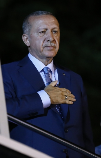 Turkey's President Recep Tayyip Erdogan gestures to supporters outside his official residence in Istanbul, Sunday, June 24, 2018. Erdogan has claimed victory in critical elections based on unofficial results, securing an executive presidency with sweeping powers. (AP Photo/Lefteris Pitarakis)