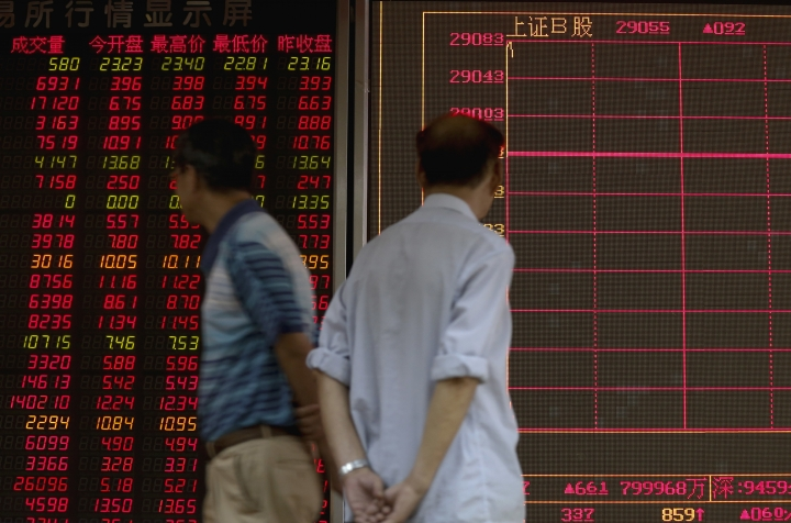 People walk while monitoring stock prices at a brokerage house in Beijing, Monday, June 25, 2018. Asian stock markets fell Monday and oil prices gave up some of their gains after Chinese regulators freed up extra money for bank lending amid a trade dispute with Washington. (AP Photo/Andy Wong)