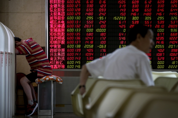 A man takes a nap near an electronic board displaying stock prices at a brokerage house in Beijing, Monday, June 25, 2018. Asian stock markets fell Monday and oil prices gave up some of their gains after Chinese regulators freed up extra money for bank lending amid a trade dispute with Washington. (AP Photo/Andy Wong)