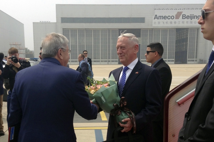 U.S. Defense Secretary Jim Mattis, center, is greeted as he arrives at Beijing Capital International Airport in Beijing, Tuesday, June 26, 2018. Mattis laid out plans for a less contentious, more open dialogue with Chinese leaders as he travels to Asia, less than a month after he slammed Beijing at an international conference for its militarization of islands in the South China Sea. (AP Photo/Lolita Baldor)