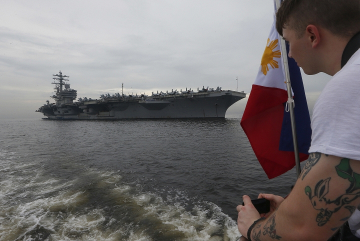 """A U.S. sailor takes photos of the U.S. aircraft carrier USS Ronald Reagan (CVN 76) as it anchors off Manila Bay for a goodwill visit Tuesday, June 26, 2018 west of Manila, Philippines. The U.S. military has deployed the U.S. aircraft carrier to patrol the South China Sea """"to deter conflict and coercion"""" in a disputed region where Washington has moved against China's military buildup on manmade islands. (AP Photo/Bullit Marquez)"""