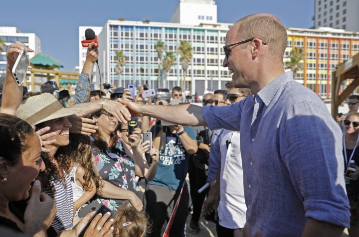 Britain's Prince William greets the crowd during a visit with Ron Huldai, the Mayor of Tel Aviv, to a beach in the coastal Mediterranean city of Tel Aviv, Israel, Tuesday, June 26, 2018. The prince is the first member of the British royal family to pay an official visit to Israel. Though the trip is being billed as non-political, the prince is meeting with Israeli and Palestinian leaders and visiting sites at the heart of the century-old conflict. (Menahem Kahana/Pool Photo via AP)