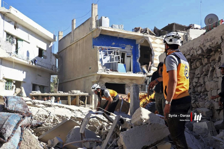 This Tuesday, June 26, 2018 photo provided by Nabaa Media, a Syrian opposition media outlet, shows civil defense workers and civilians inspecting damaged buildings that were hit by Syrian government forces bombardment, in Daraa, southern Syria. International aid organizations sounded the alarm Wednesday for the fate of thousands of desperate Syrians fleeing the onslaught of President Bashar Assad's forces in southwestern Syria, urging neighboring countries to take them in. (Nabaa Media, via AP)