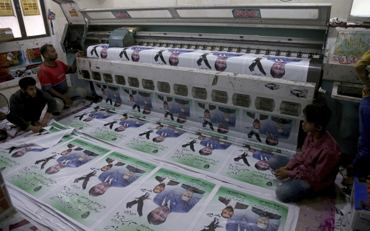 Pakistani workers print posters of candidates for the upcoming parliamentary elections at a print shop in Karachi, Pakistan, Tuesday, June 26, 2018. Pakistan is scheduled to hold parliamentary elections on July 25, that will mark the first time the country has held three consecutive elections without a coup. (AP Photo/Shakil Adil)