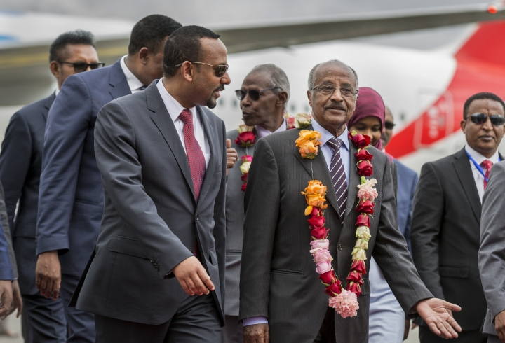Eritrea's Foreign Minister Osman Sale, center-right, is welcomed by Ethiopia's Prime Minister Abiy Ahmed, center-left, upon the Eritrean delegation's arrival at the airport in Addis Ababa, Ethiopia Tuesday, June 26, 2018. The delegation of top officials from Eritrea arrived Tuesday for the first peace talks in 20 years and were welcomed at the airport by Ethiopian Prime Minister Abiy Ahmed, signifying the importance of their visit. (AP Photo/Mulugeta Ayene)