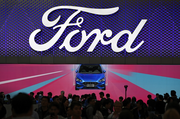 FILE - In this file photo taken Wednesday, April 25, 2018, visitors and journalists crowd near a Ford Focus on display at the Ford exhibit during the media day for the China Auto Show in Beijing. China has eased limits on foreign ownership in auto manufacturing, insurance, and other fields but didn't directly address complaints that are fueling conflict with Washington over trade and technology. (AP Photo/Andy Wong, File)