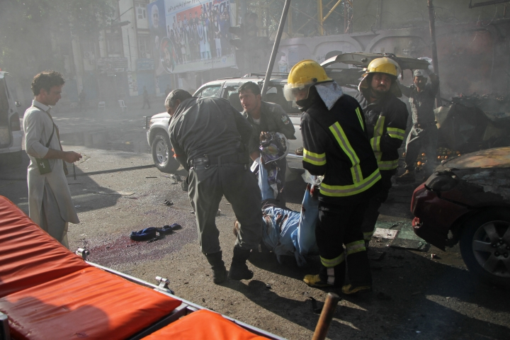 Emergency personnel remove a body at the site of a deadly suicide attack in Jalalabad, Afghanistan Thursday, June 7, 2018. A suicide bomber targeted a group of Sikhs and Hindus on their way to meet Afghanistan's president in the eastern city of Jalalabad on Sunday, killing at least 19 people including Avtar Singh Khalsa, a longtime leader of the Sikh community who had planned to run in the parliamentary elections set for October. (AP Photo)