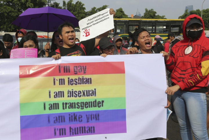 "FILE - In this Feb. 12, 2018, file photo, LGBT activists shout slogans during a rally against a planned revision to Indonesia's criminal code that would criminalize unmarried and gay sex outside the Parliament in Jakarta, Indonesia. The death of a 20-year-old man with HIV who died after ""effectively committed suicide"" by stopping anti-viral medication is a sign of an out of control but little acknowledged epidemic of HIV among gay men in Indonesia that researchers say is now being fueled by a gay hate climate fostered by the country's conservative political and religious leaders. (AP Photo/Tatan Syuflana, File)"