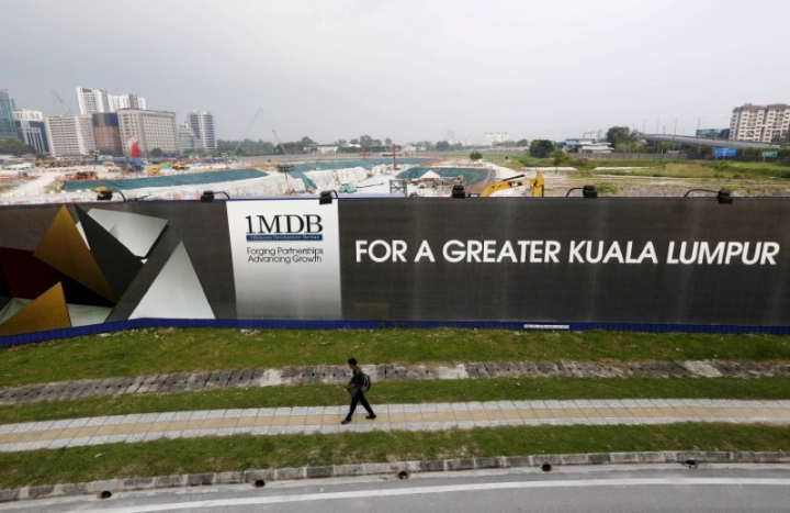 FILE PHOTO - A man walks past a 1 Malaysia Development Berhad (1MDB) billboard at the funds flagship Tun Razak Exchange development in Kuala Lumpur, March 1, 2015.     REUTERS/Olivia Harris/File Photo