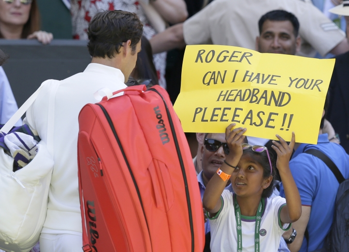 A fan holds a banner next to Roger Federer of Switzerland, asking for his headband, at the end of his Men's Singles first round match against Serbia's Dusan Lajovic at the Wimbledon Tennis Championships in London, Monday July 2, 2018. (AP Photo/Tim Ireland)