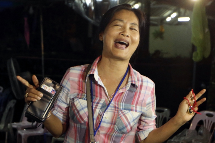 A family member smiles after hearing the news that the missing 12 boys and their soccer coach have been found, in Mae Sai, Chiang Rai province, in northern Thailand, Monday, July 2, 2018. A Thai provincial governor says all 12 boys and their coach have been found alive in the cave where they went missing over a week ago in northern Thailand. (AP Photo/Sakchai Lalit)