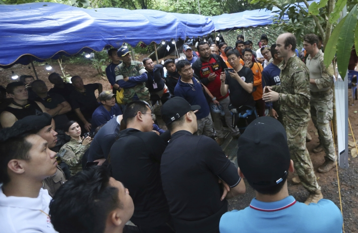 Personnels, right, of U.S. Special Operations Command Pacific Search and Rescue team meet with rescue teams from China, Thailand and Australia as they conduct search operation for missing 12 boys and their soccer coach, in Mae Sai, Chiang Rai province, in northern Thailand, Monday, July 2, 2018. Rescue divers are advancing in the main passageway inside the flooded cave in northern Thailand where the boys and their coach have been missing more than a week. (AP Photo/Sakchai Lalit)