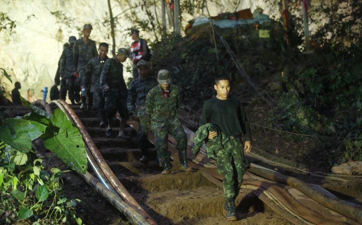 Rescuers make their way down at the entrance to a cave complex where 12 boys and their soccer coach went missing, in Mae Sai, Chiang Rai province, in northern Thailand, Monday, July 2, 2018. Rescue divers are advancing in the main passageway inside the flooded cave in northern Thailand where the boys and their coach have been missing more than a week. (AP Photo/Sakchai Lalit)