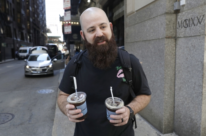 Adam Taylor, a sound engineer from Las Vegas carries two glasses of iced coffee, responds to a question about new research showing that drinking coffee may boost chances for a longer life, even for those who down at least eight cups daily Monday, July 2, 2018, in Chicago. In a study of nearly half-a-million British adults, coffee drinkers had a slightly lower risk of death over 10 years than abstainers. (AP Photo/Charles Rex Arbogast)