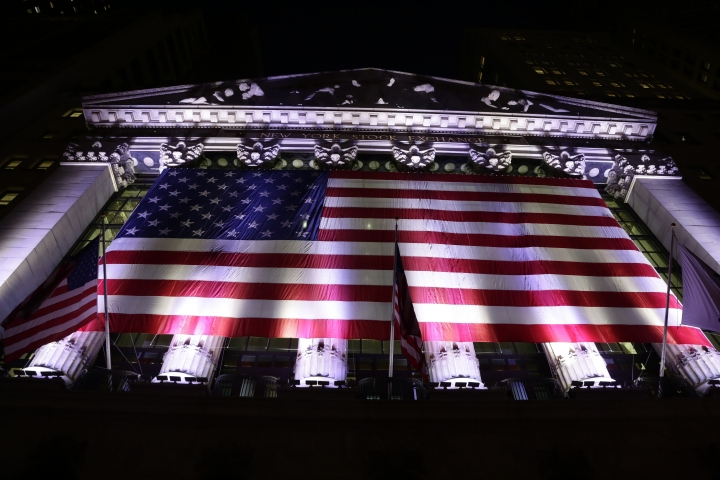 FILE- In this Feb. 17, 2017, file photo, an American flag hangs on the front of the New York Stock Exchange. The U.S. stock market opens at 9:30 a.m. EDT on Tuesday, July 3, 2018. (AP Photo/Peter Morgan, File)