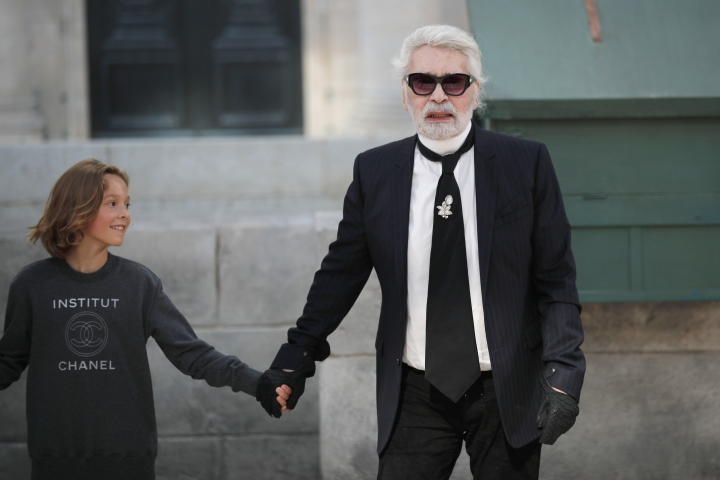 Designer Karl Lagerfeld, right, holds the hand of model Hudson Kroenig after the Chanel Haute Couture Fall-Winter 2018/2019 fashion collection presented Tuesday, July 3, 2018 in Paris. (AP Photo/Francois Mori)
