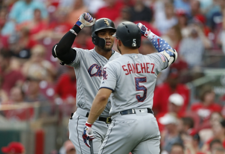 Chicago White Sox's Yoan Moncada, left, celebrates a two-run home run off Cincinnati Reds starting pitcher Sal Romano with Yolmer Sanchez during the third inning of a baseball game Wednesday, July 4, 2018, in Cincinnati. (AP Photo/Gary Landers)