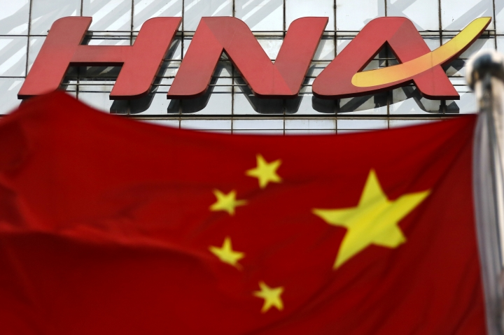 In this Feb. 6, 2017, photo, a Chinese national flag flutters against the HNA Group office building in Beijing. Chinese conglomerate HNA Group, which operates Hainan Airlines and other businesses around the world, says its co-chairman has died on Tuesday, July 3, 2018, while on a business trip to France. (AP Photo/Andy Wong)
