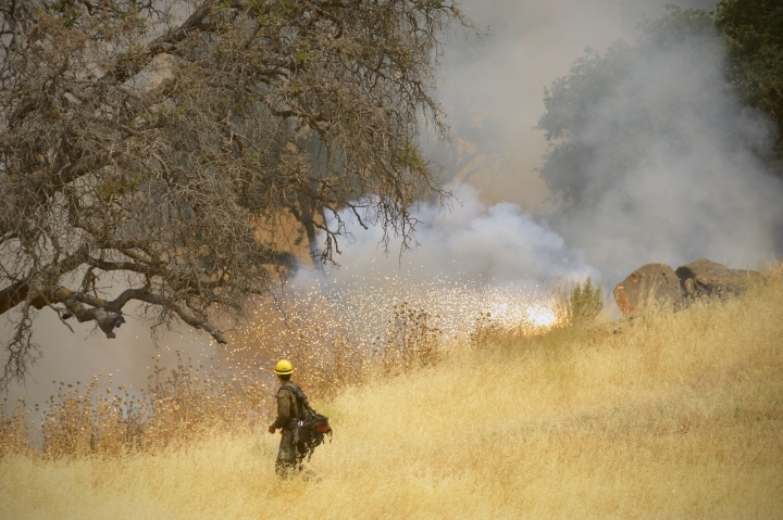 Hot Shot crews from Truckee use incendiary devices to start backfires to help contain the County Fire along Highway 129 near Lake Berryessa in Yolo County, California, Tuesday, July 3, 2018. (Randall Benton/The Sacramento Bee via AP)