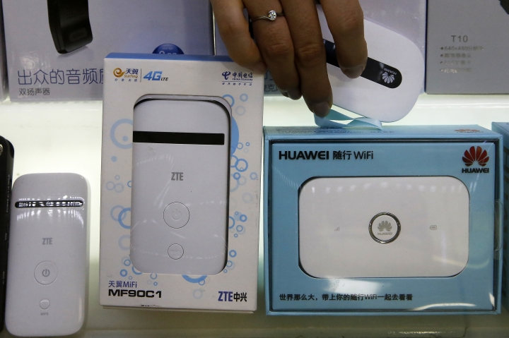 A worker takes a Huawei mobile Internet device next to it competitor ZTE Corp, left, which are displayed for sale at a computer mall in Beijing Wednesday, July 4, 2018. Tech giant ZTE Corp.'s near-death experience after Washington barred it from buying U.S. components was a stark reminder that China's industry leaders cannot function without American technology. (AP Photo/Andy Wong)