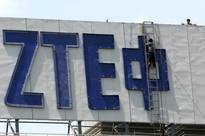 FILE - In this April 18, 2007, file photo, workers install the logo for ZTE, a leading Chinese communications company, on top of an office building in Nanjing in eastern China's Jiangsu province. Tech giant ZTE Corp.'s near-death experience after Washington barred it from buying U.S. components was a stark reminder that China's industry leaders cannot function without American technology. (Chinatopix via AP, File)