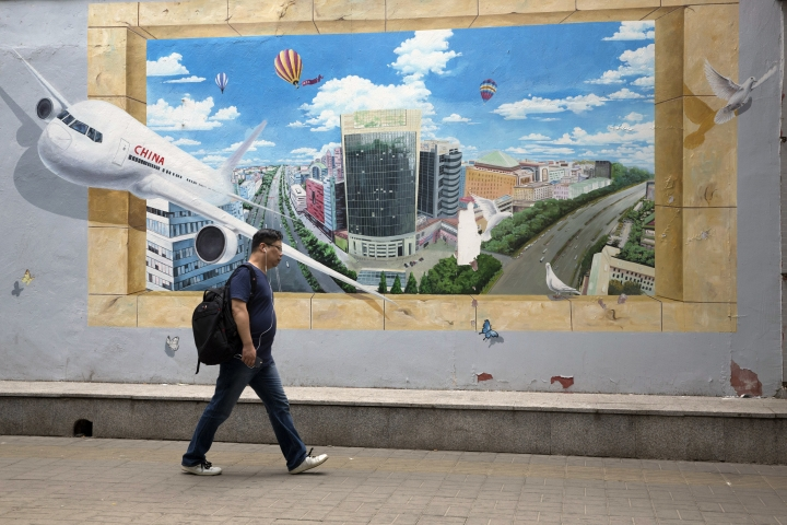 In this Tuesday, July 3, 2018, photo, a man walks past a mural depicting a prosperous city and a Chinese airliner in Beijing. Despite the threat from U.S. President Donald Trump of tariff hikes on up to $450 billion of Chinese goods, Beijing shows no sign it will scale back plans it sees as a path to prosperity and global influence. (AP Photo/Ng Han Guan)