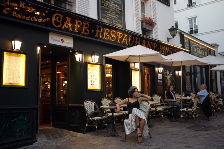 "In this photo taken on Monday, June 25, 2018, Anna Amurova from Russia strikes a pose at ""La Bonne Franquette"" restaurant where Vincent Van Gogh was inspired for the 1886 oil painting ""La Guinguette"", at Montmartre district, in Paris. Paris' bistros and terraces have formed an association of bistros owners to launch a campaign to be recognized by the United Nations' cultural agency UNESCO as a French way of life with ""intangible cultural heritage"" status. (AP Photo/Francois Mori)"