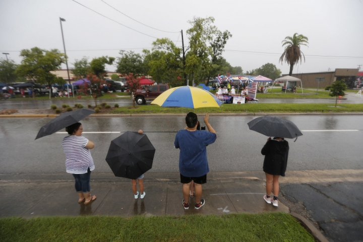 People watch the Friendswood Grand Parade during heavy rain on Wednesday, July 4, 2018, in Friendswood, Texas. (Steve Gonzales/Houston Chronicle via AP)