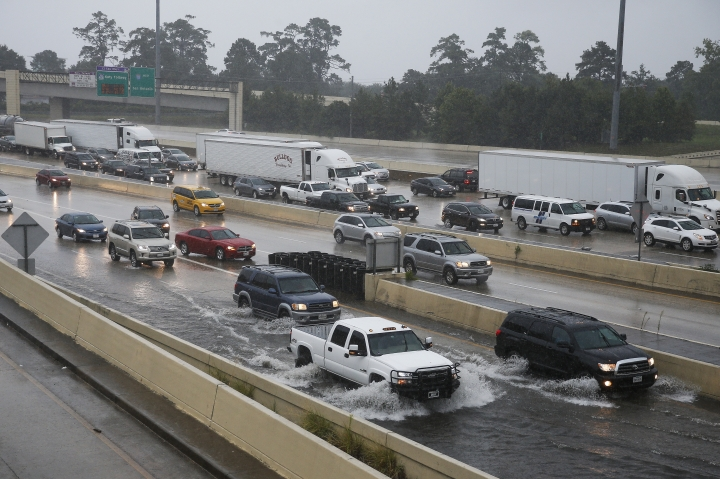 Cars drive through high water on the exit ramp to southbound 610 from eastbound Interstate-10 on Wednesday, July 4, 2018, in Houston. Heavy rains that flooded some Houston streets on July Fourth are expected to subside. (Michael Ciaglo/Houston Chronicle via AP)