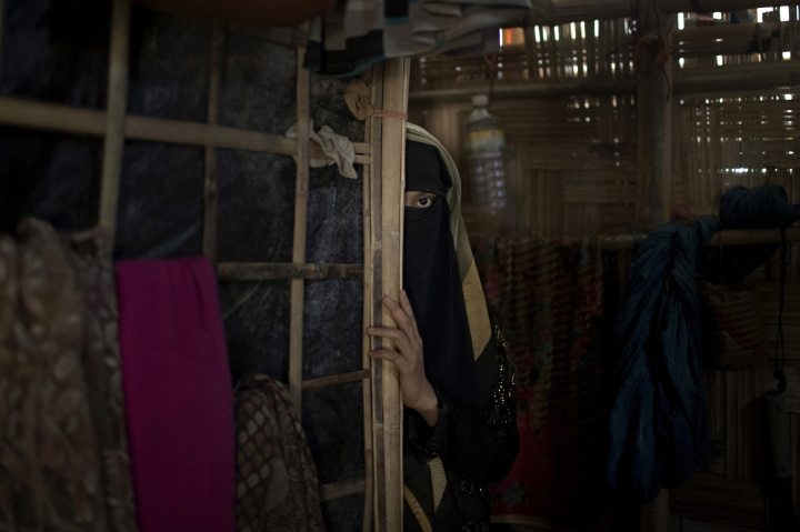 """In this Tuesday, June 26, 2018, photo, """"A,"""" a 13-year old Rohingya Muslim girl who agreed to be identified by her first initial, peers from behind a partition in her family's shelter in Jamtoli refugee camp in Bangladesh. Two months earlier, soldiers had broken into her home back in Myanmar and raped her, an attack that drove her and her terrified family over the border to Bangladesh. Ever since, she had waited for her period to arrive. Gradually, she came to realize that it would not. The pregnancy was a prison she was desperate to escape. The rape itself had destroyed her innocence. But carrying the baby of a Buddhist soldier could destroy her life. (AP Photo/Wong Maye-E)"""