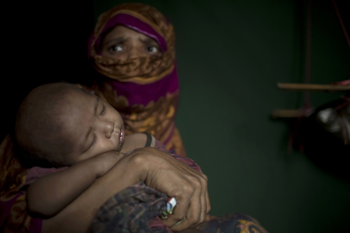"""In this Monday, June 25, 2018, photo, """"S"""" holds her baby boy as she sits in her shelter in Balukhali refugee camp in Bangladesh. """"S,"""" a widow, was so worried about her neighbors discovering her pregnancy that she suffered silently through labor in her shelter, stuffing a scarf in her mouth to swallow her screams. (AP Photo/Wong Maye-E)"""