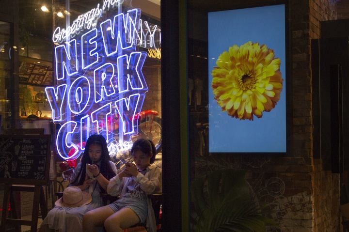 "In this Thursday, July 5, 2018 photo, girls sit in front of an American cosmetics brand's shop window display reading ""Greetings from New York City"" at a shopping mall in Beijing. In its official discourse, China says it's girded for a trade war with the U.S. and can give as good as it gets. Elsewhere, the message is less sanguine. A decline in the stock market and expressions of concern among some academics point to an underlying anxiety over the trade friction that contradicts Beijing's confident posture. (AP Photo/Mark Schiefelbein)"