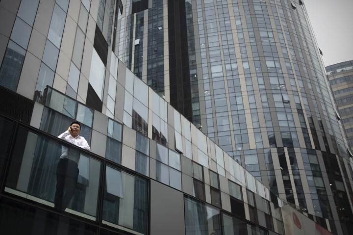 In this Thursday, July 5, 2018 photo, a man talks on his smartphone as he stands outside of an office building and shopping complex in Beijing. In its official discourse, China says it's girded for a trade war with the U.S. and can give as good as it gets. Elsewhere, the message is less sanguine. A decline in the stock market and expressions of concern among some academics point to an underlying anxiety over the trade friction that contradicts Beijing's confident posture. (AP Photo/Mark Schiefelbein)