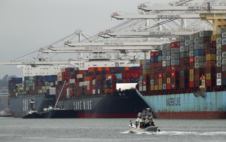 In this July 2, 2018, photo container ships are unloaded at the Port of Oakland in Oakland, Calif. On Friday, July 6, the Commerce Department reports on the U.S. trade gap for May. (AP Photo/Ben Margot, File)