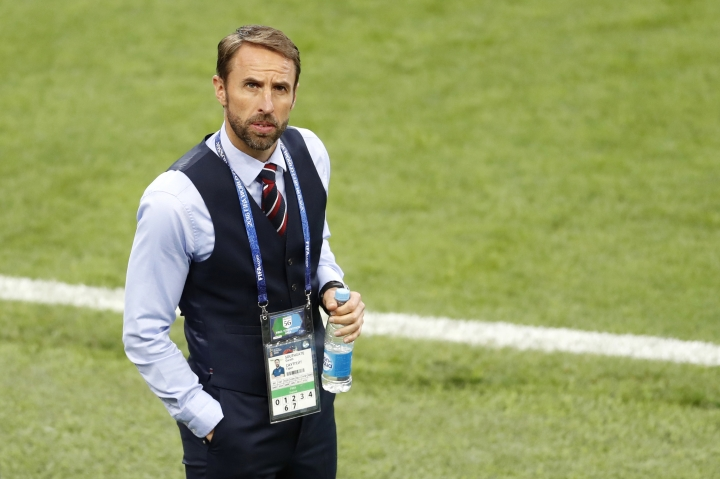 FILE - In this Tuesday, July 3, 2018 file photo England head coach Gareth Southgate looks up to the stands during warmup before the round of 16 match between Colombia and England at the 2018 soccer World Cup in the Spartak Stadium, in Moscow, Russia. Gareth Southgate may do for the vest what Britain's then-future King Edward VII did for the tuxedo. Bereft of suit jacket, the England manager walks the sidelines at the World Cup in navy suit trousers and waistcoat with a blue shirt and a red, white and blue striped silk tie, instantly recognizable in a profession where casual has become common. (AP Photo/Antonio Calanni, File)