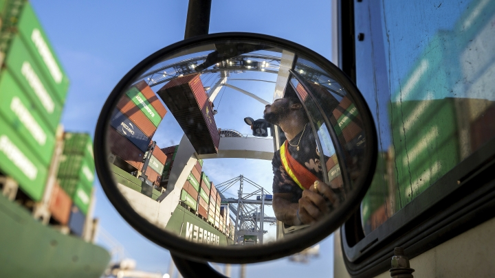 In this June, 19, 2018 photo, a jockey truck driver waits for his load of a shipping container to clear his trailer as a shore crane lifts the 40-foot onto the container vessel Ever Linking at the Port of Savannah in Savannah, Ga. The U.S. has threatened to impose 25 percent duties on $34 billion in Chinese products starting Friday, July 6, and China has said it will fire back with corresponding tariffs. (AP Photo/Stephen B. Morton)