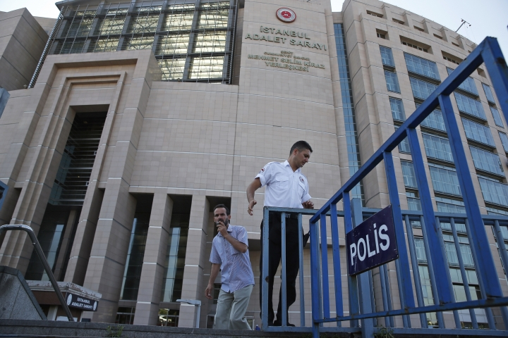 A security guard adjusts barriers outside a court where the trial of journalists of the now-defunct Zaman newspaper on charges of aiding terror groups was held, in Istanbul, Friday, July 6, 2018. A court in Istanbul has convicted six journalists of terror-related charges, sentencing them to lengthy prison terms in a case that had heightened concerns over freedoms of expression and media. The court, however, on Friday acquitted five other journalists of the now-defunct Zaman newspaper, which was close to U.S.-based cleric Fethullah Gulen, whom Turkey blames for a failed coup in 2016. Gulen denies involvement. (AP Photo/Lefteris Pitarakis)