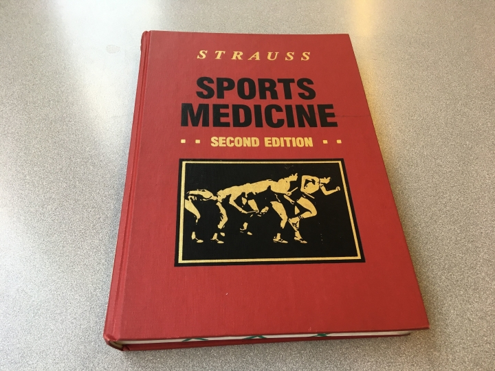 In this Monday, July 2, 2018, photo, a book edited by Dr. Richard Strauss sits on a table inside the Health Science Library on the campus of Ohio State University in Columbus, Ohio. Independent investigators are reviewing allegations against Strauss by men from 14 sports at the university. Some of the men tell The Associated Press they were molested by Strauss and describe him as a locker-room voyeur who unnecessarily groped athletes during medical exams and wasn't stopped by administrators even after students complained about his behavior. (AP Photo/Mike Householder)