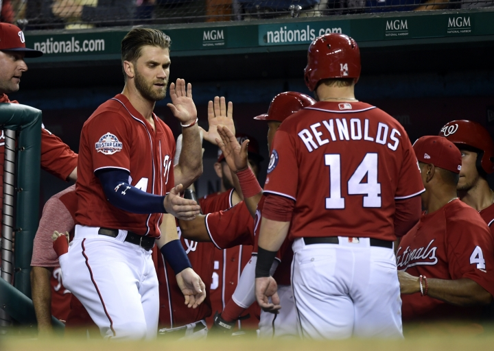 Washington Nationals' Bryce Harper, second from left, reaches out to congratulate teammate Mark Reynolds, (14) after Reynolds hit a two-run home run against the Miami Marlins in the second inning of a baseball game at Nationals Park in Washington, Saturday, July 7, 2018. (AP Photo/Susan Walsh)