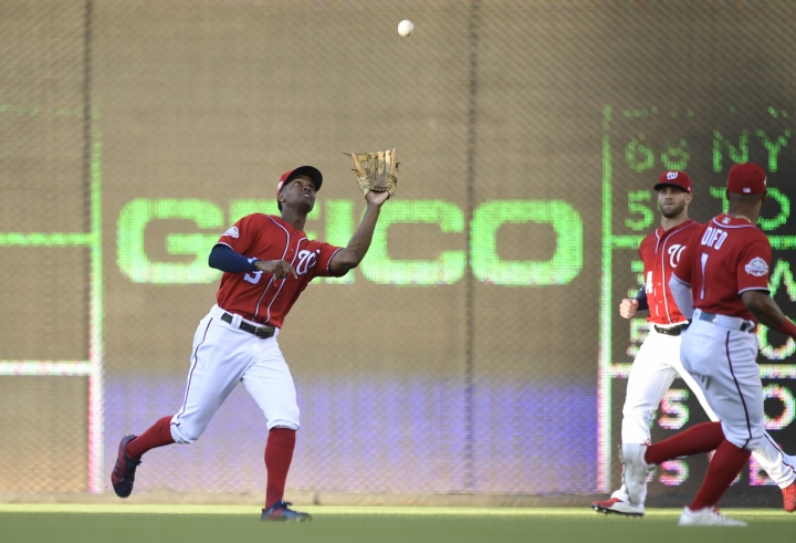 Washington Nationals center fielder Michael Taylor (3) catches a fly ball hit by Miami Marlins' Starlin Castro during the first inning of a baseball game at Nationals Park in Washington, Saturday, July 7, 2018. Nationals right fielder Bryce Harper, second from right, and shortstop Wilmer Difo, right, watch the play. (AP Photo/Susan Walsh)