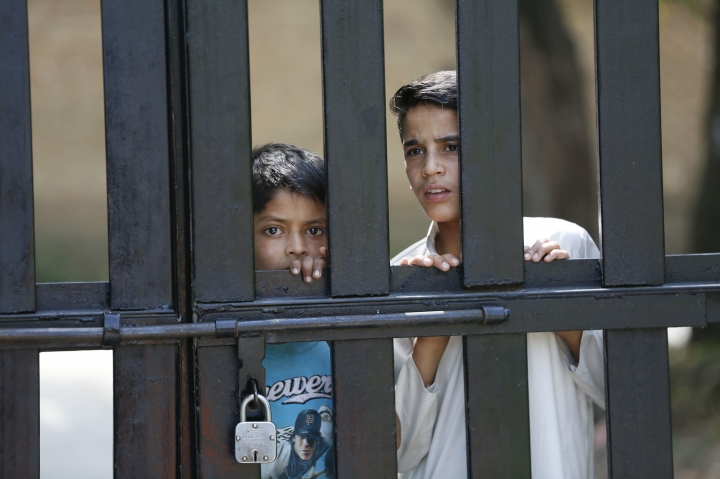 Kashmiri young boys watch behind a closed gate as students protest inside the Kashmir University campus in Srinagar, Indian controlled Kashmir, Sunday, July. 8, 2018. Armed police and soldiers fanned out across much of Indian-controlled Kashmir to enforce a security lockdown on Sunday as separatists challenging Indian rule called for a shutdown and protests on the second anniversary of the killing of a charismatic rebel leader. (AP Photo/Mukhtar Khan)