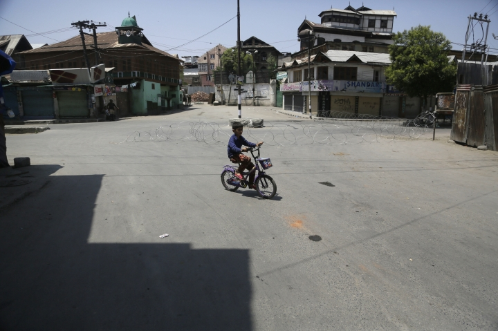 A child rides his bicycle through a closed market during a general strike in Srinagar, Indian controlled Kashmir, Sunday, July. 8, 2018. Armed police and soldiers fanned out across much of Indian-controlled Kashmir to enforce a security lockdown on Sunday as separatists challenging Indian rule called for a shutdown and protests on the second anniversary of the killing of a charismatic rebel leader. (AP Photo/Mukhtar Khan)