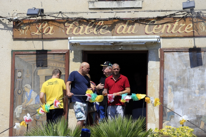 Spectators stand in a restaurant prior to the start of the second stage of the Tour de France cycling race over 182.5 kilometers (113.4 miles) with start in Mouilleron-Saint-Germain and finish in La Roche Sur-Yon, France, Sunday, July 8, 2018. (AP Photo/Peter Dejong)