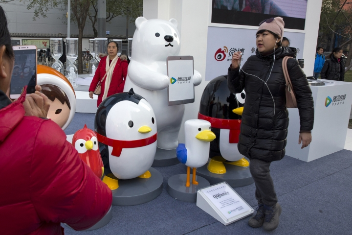 In this Nov. 20, 2017, photo, a woman wears her earphones as she walks past mascots representing the various platforms owned by Chinese internet conglomerate Tencent Holdings Limited during a promotion of Tencent Video, a video streaming service, in Beijing, China. Tencent, China's most valuable tech company and the operator of the popular WeChat social media platform, says it plans to spin off its streaming music service on a U.S. stock exchange. (AP Photo/Ng Han Guan)