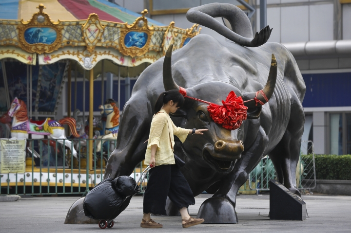 A woman pulls a 2 wheel trolley loaded with goods touches a bull statue on display outside a retail and wholesale clothing mall in Beijing, Monday, July 9, 2018. The trade war that erupted last Friday between the U.S. and China carries a major risk of escalation that could weaken investment, depress spending, unsettle financial markets and slow the global economy. (AP Photo/Andy Wong)