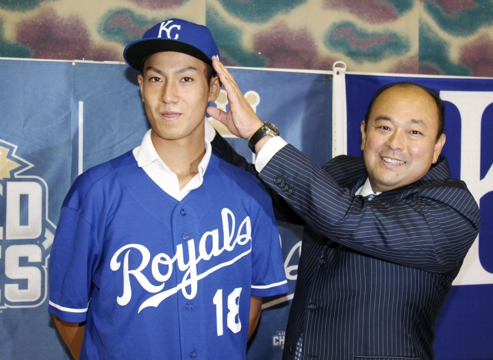 In this July 8, 2018, photo, Kaito Yuki, left, poses with Hiroyuki Oya, a Royals international scout, for photographers at a press conference in Osaka, western Japan. Yuki is headed to the Kansas City Royals organization instead of attending high school in Japan. The team signed Yuki, a 16-year-old pitcher, out of junior high to a standard seven-year minor league contract Sunday. He is thought to be the first Japanese junior high school player to sign with a major league club. (Kyodo News via AP)